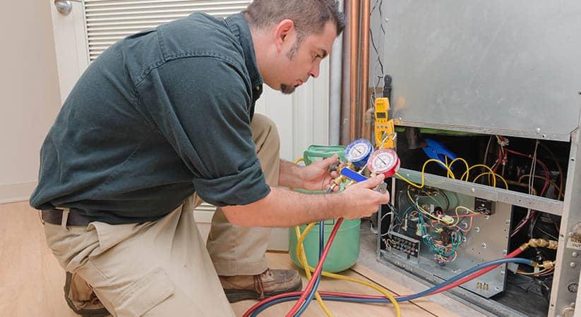 HVAC technician charging a heat pump with refrigerant