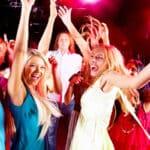 Joyful teens having fun in night club while dancing