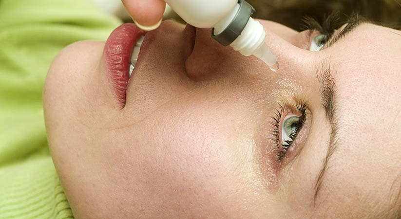Girl dripping eye with eyes drops