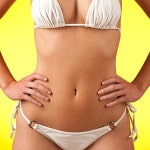 Slim female body with white bikini on yellow background