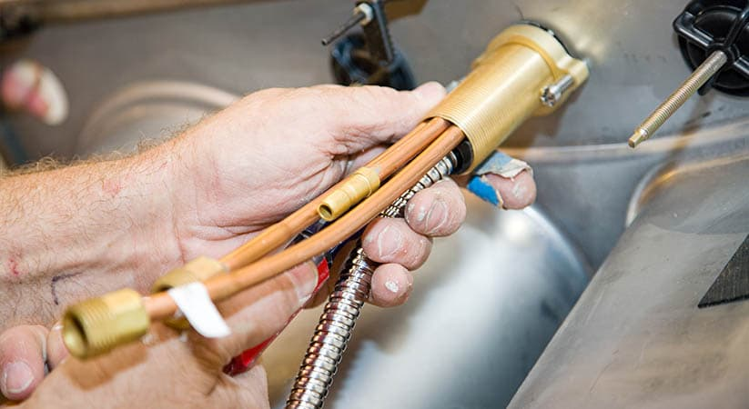 Closeup of a plumbers hands installing a faucet in a sink.